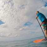 A happy student learning to surf on a stand-up paddleboard in Rincon, Puerto Rico.
